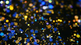 Defocused shimmering multicolored glitter confetti, black background. Holiday abstract festive bokeh light spots. Defocused shimmering multicolored glitter stock video footage