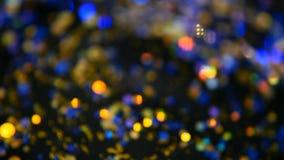 Defocused shimmering multicolored glitter confetti, black background. Holiday abstract festive bokeh light spots. Defocused shimmering multicolored glitter stock video