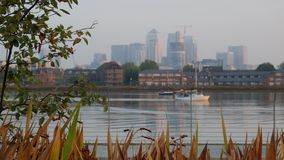 Defocused shot of Canary Wharf as a yacht passes stock video footage