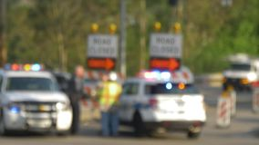 Defocused Blocked Road at Construction Site. 8493 Defocused shot of a closed road with a police car blocking the street as cars pass by stock footage