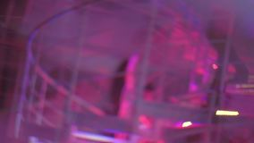 Defocused shot of party people walking up and down stairs in popular night club. Stock footage stock footage
