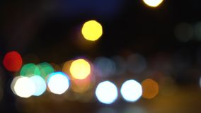 Defocused or soft focus bokeh lights of cars, scooters, motorbikes and traffic driving on city streets at night. Defocused or soft focus bokeh lights of vehicles stock video footage