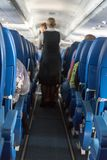 The defocused stewardess serve refreshments in the aircraft. The defocused stewardess serve refreshments on board the aircraft. An view at the corridor of the royalty free stock image