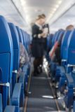 The defocused stewardess serve refreshments. On board the aircraft. An view at the corridor of the airplane royalty free stock image