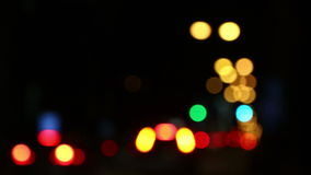 Defocused traffic lights of the night city road. Defocused bokeh of colourful traffic lights of the night city road stock video