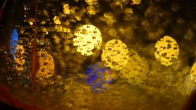 Defocused traffic lights through wet car glass. Rainy night. Relection in wing mirror. Colorful abstract background stock footage
