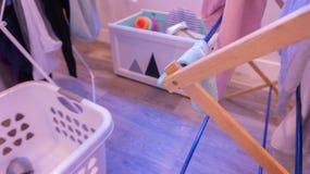 Defocused tvätteriplats i inomhus vardagsrum, med kläder på att torka kuggar, tvättkorgen och leksakslådan royaltyfri bild