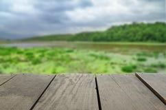 Defocused und Unschärfebild der Terrassenholz- und Seelandschaftsansicht Stockfotografie
