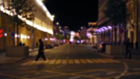 Defocused view of the night city street. Cars drive along the road. People walk