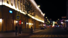 Defocused view of the night city street. Cars drive along the road. People walk. Defocused view of the city street. Night time. People are standing at the stock video