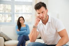 Defocused woman in front of sad young man Royalty Free Stock Images