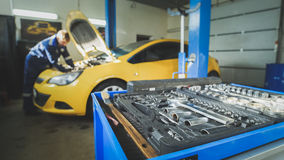 Defocused - a worker mechanic checks the electrical in the hood of the yellow car, garage workshop Stock Photos