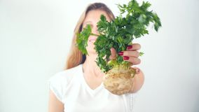 Defocused young woman showing fresh celery root. Defocused young woman holding in hands with red manicure fresh celery root stock footage