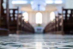 Defocusedbinnenland van Katholieke kerk met banken stock foto
