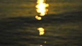 Defocusedlichten van zonsopgang over een oceaan. golven en oranje kleur stock footage