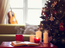 Defocusing guitar on the window . Defocuinfs guitar on the window with Christmas tree, hot red cup , book and candles infront of her stock images