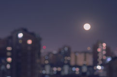 Defocusl-Mond-Aufstieg über Stadt nachts lizenzfreies stockbild