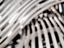 Defocussed background of a  woven steel tube pattern Stock Image