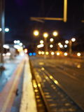 Defocussed railway track with platform and lights at night Royalty Free Stock Images