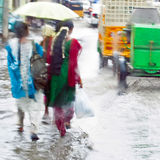 Defocussed view of flash flood at Indian city street. With auto rickshaw, bicycles and pedestrians after monsoon rain. India, Tamil Nadu royalty free stock images