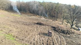 Deforestation. Flight over the clearing where deforestation takes place. Trctor moves to the forest. Smoke in the forest