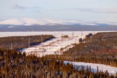Deforestation under power line on background of snow-capped mountains, winter.  stock photo