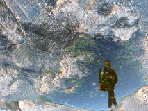 Deformed reflection of a person. In a puddle of water and framed in the lower right corner Royalty Free Stock Photos