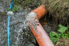 Deformed water pipe burst water flowing out of it.  royalty free stock photo