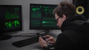 Defraudador do Internet que reflashing o smartphone roubado para obter dados de usuário O hacker olha o tela de computador e lê-o vídeos de arquivo