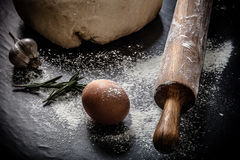 Deg på ett svart bräde med mjöl ägg kavel, vitlök Si Royaltyfri Foto