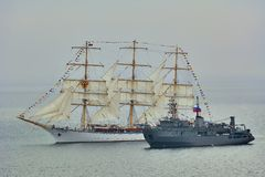 Degaussing ship next to the Sailing one Royalty Free Stock Photography