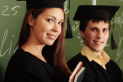 Degree. Educational theme: graduating students in academic gown in a classroom Stock Photos