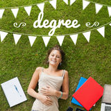 Degree against pretty student lying on grass Royalty Free Stock Photography