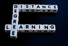 Degree by distance learning. Text ' degree ', ' distance ' and ' learning ' inscribed on small white cubes in black uppercase letters and arranged crossword stock photo