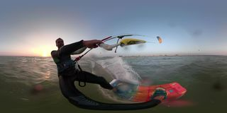 A man in a suit for diving deals with kitesurfing, in the background a beach camp. 360 degrees, a man in a suit for diving glides on the sea engaged kitesurfing stock footage