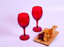 Two red wine glasses and dry mango stock image