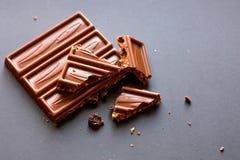 Degustation de la confitería Pedazos de chocolate con leche con las avellanas y las pasas machacadas con alcohol en fondo negro foto de archivo