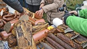 Degustation e cineoperatore delle salsicce di bacon sul lavoro Fotografia Stock