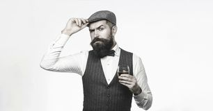 Degustation, Probieren Mann mit Bart hält Glas Weinbrand Tragender Anzug des bärtigen Mannes und trinkender Whisky, Weinbrand stockbild