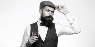 Degustation, prueba El hombre con la barba sostiene el vidrio de brandy Prueba, concepto del degustation Hombre de negocios barbu fotos de archivo libres de regalías