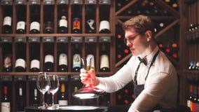 Degustatore o degustator del vino che versa vino rosso nella caraffa per fare colore perfetto archivi video