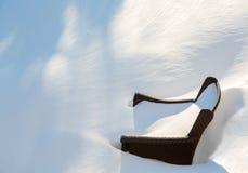 Dehors chaise de jardin enterrée dans la dérive de neige Image stock