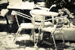 Dehors la table et les chaises de jardin enterrées dans la neige dérivent Photo stock