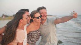 Dehors portrait de deux couples prenant Selfie par le téléphone portable sur le bord de la mer pendant la Windy Weather clips vidéos