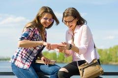 Dehors portrait des amis féminins posant dans la rue avec le téléphone Fond urbain, rivière, ciel Photo libre de droits