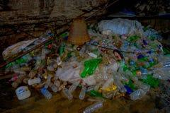 DEHRA DUN, INDIEN - 7. NOVEMBER 2015: Schließen Sie oben vom Abfall mit Plastikflaschen, Körbe, Säcke in Tapkeshwar Mahadev Stockbilder