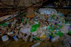 DEHRADUN, INDIA - NOVEMBER 07, 2015: Sluit omhoog van huisvuil met plastic flessen, manden, zakken in Tapkeshwar Mahadev Royalty-vrije Stock Foto