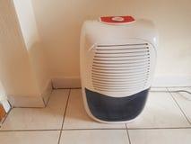 Dehumidifier on the floor white red plastic stock photos