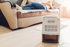 Dehumidifier with touch panel, humidity indicator, uv lamp, air ionizer, water container works in apartment. Close up royalty free stock photography