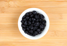Dehydrated blueberries in bowl against wood Royalty Free Stock Image